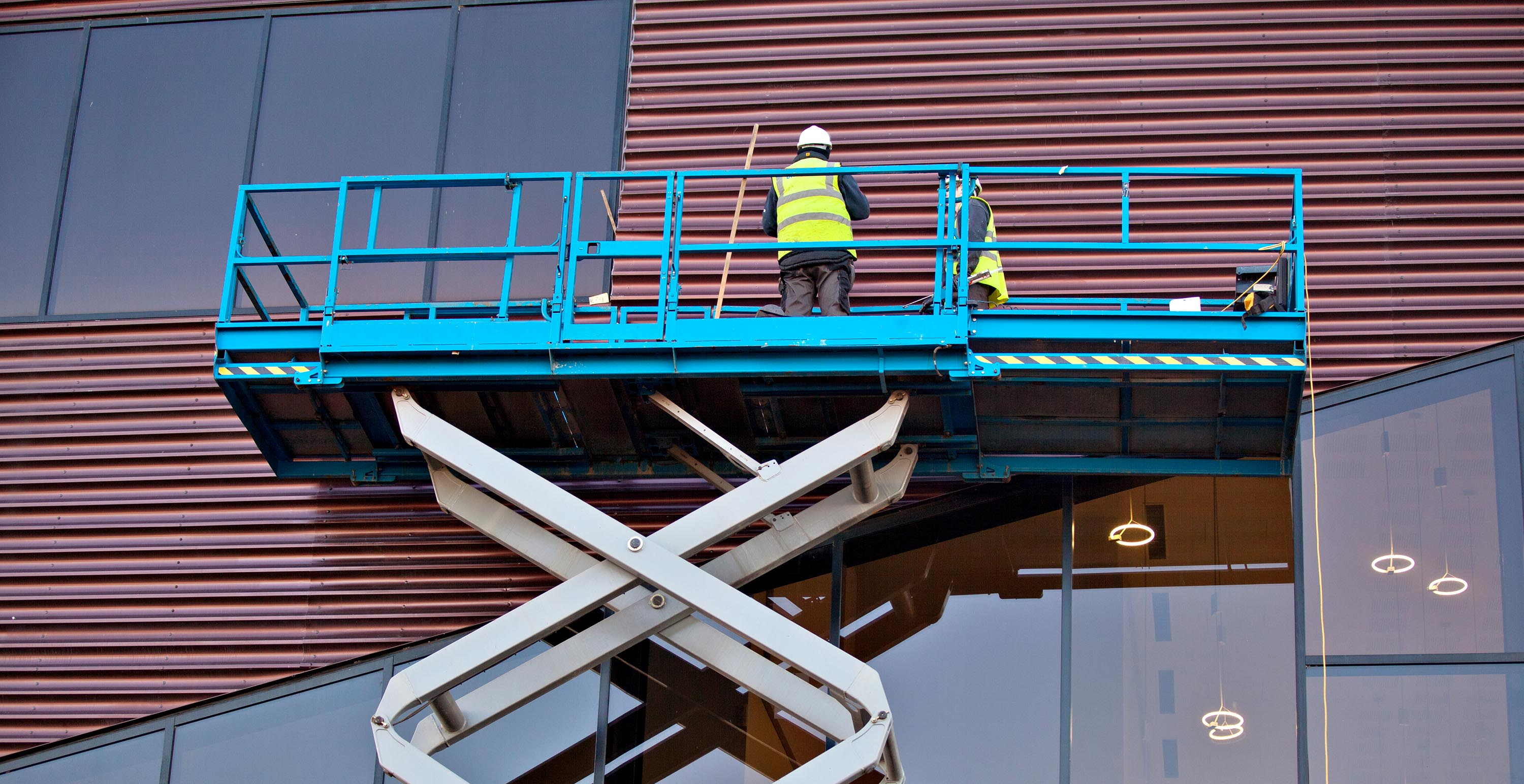 Builder on a Scissor Lift Platform at a construction site.